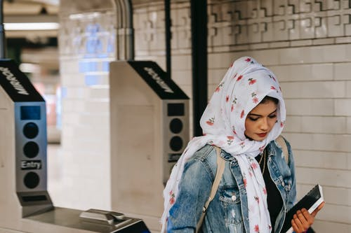 Calm Muslim woman walking through subway gate