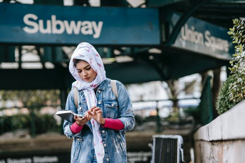 Serious ethnic woman messaging via smartphone while standing near subway