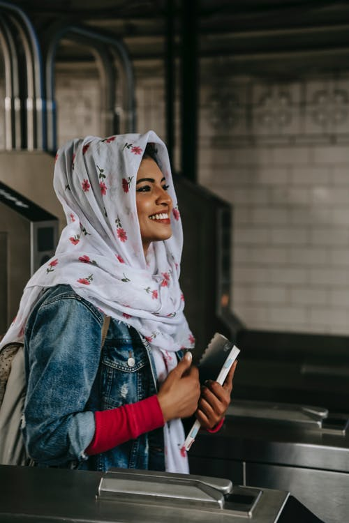 Smiling ethnic woman with copybook wearing hijab entering subway