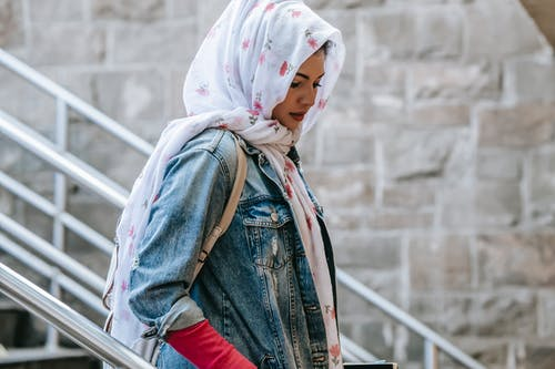 Muslim woman descending stairs to subway