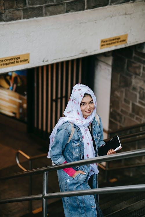 Cheerful Muslim woman climbing stairs