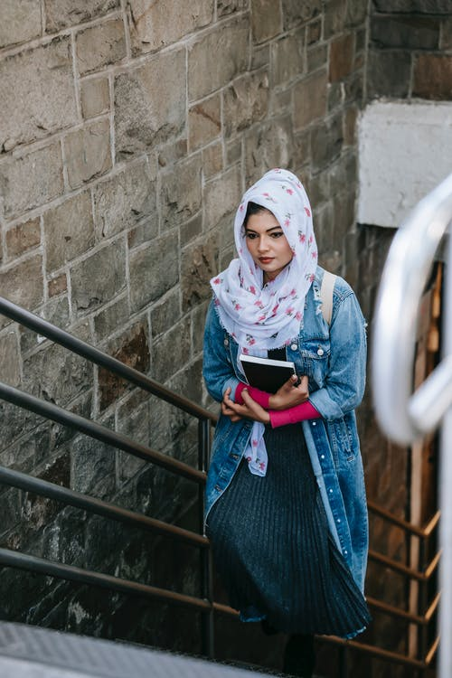 Young Muslim woman ascending staircase