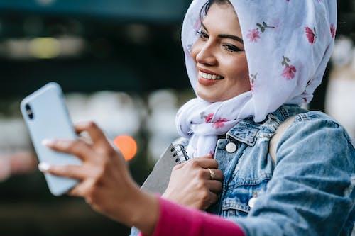 Cheerful Muslim woman taking selfie