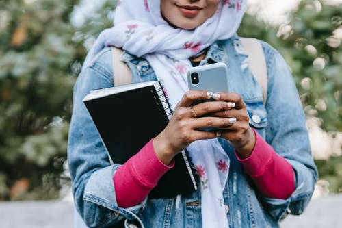 Crop anonymous female in headscarf and jeans jacket with rolled up sleeves and with notebook messaging on cellphone