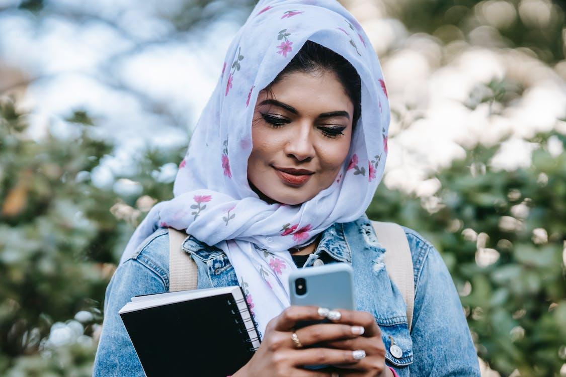 Cheerful Muslim woman with smartphone