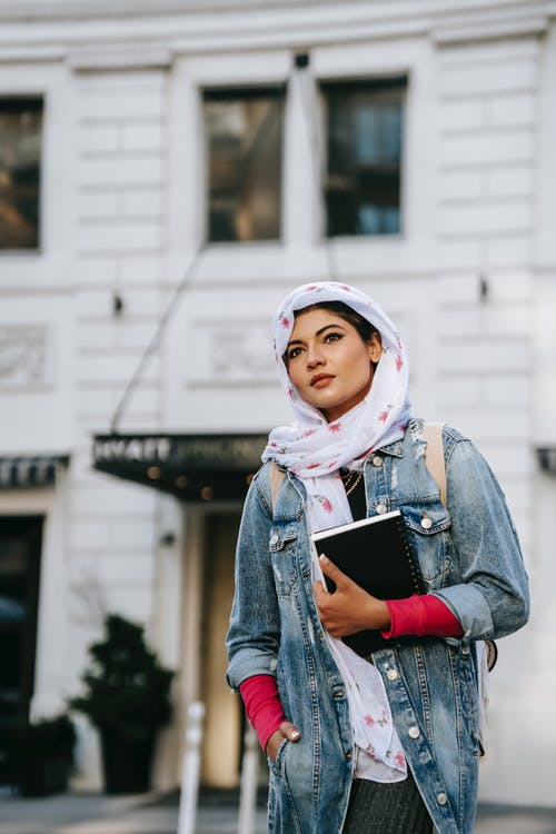 Woman in headscarf against building