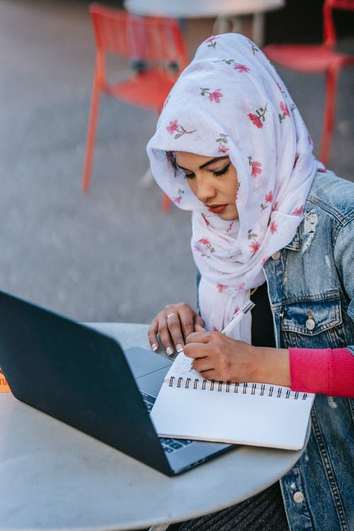 Muslim woman with laptop and notebook