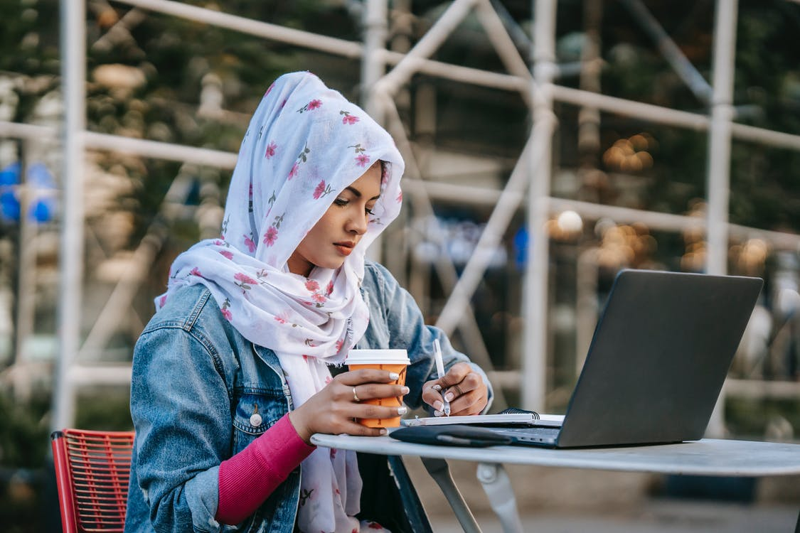 Focused Muslim female in headscarf and denim jacket taking notes from laptop while working and drinking coffee
