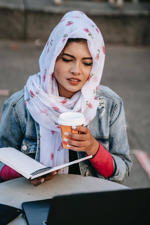 Young ethnic woman in headscarf with coffee studying