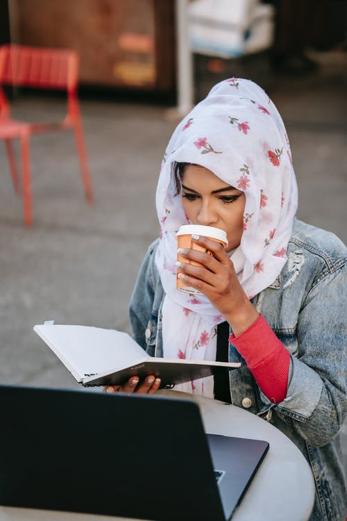 Young ethnic woman drinking coffee and comparing information