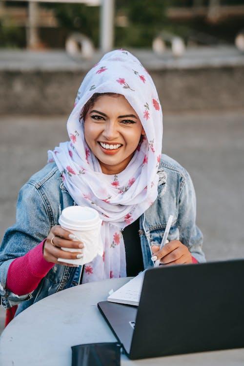 Positive Muslim freelancer with takeaway coffee working on street
