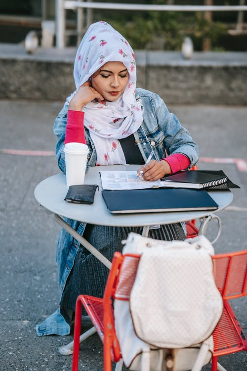 Thoughtful Muslim woman freelancer in headscarf sitting at table on street and taking notes in documents in daytime