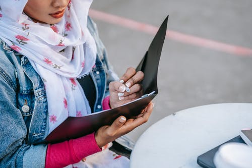Pensive Muslim female in casual clothes and light headscarf sitting at table on street and taking notes in documents in daytime