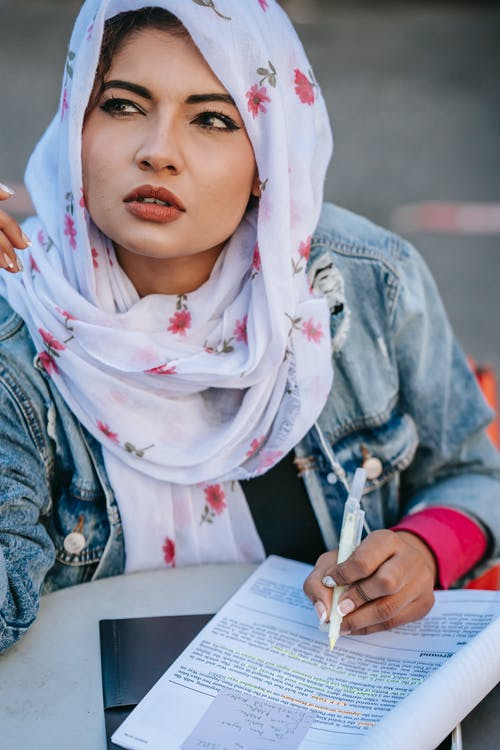 Pensive Muslim female sitting at table with documents and looking away
