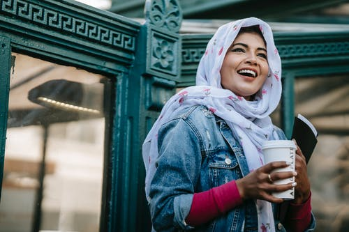 Happy Muslim lady with takeaway coffee standing against ornamental construction