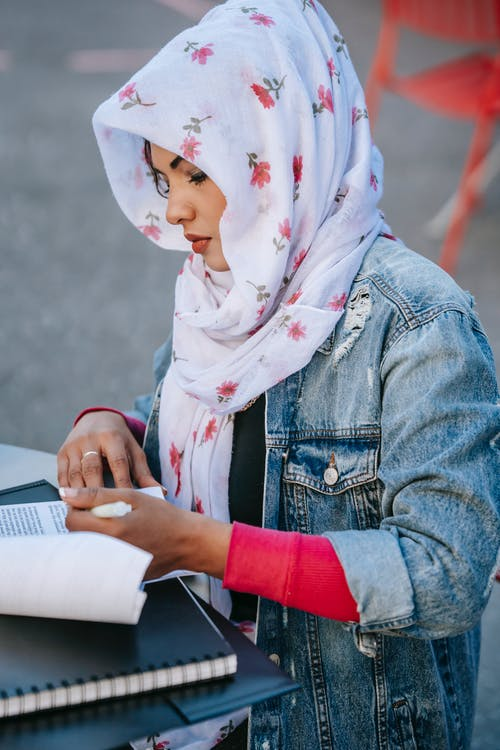 Side view of concentrated Muslim woman entrepreneur in casual clothes and  headscarf sitting at table and reading report on street in daylight