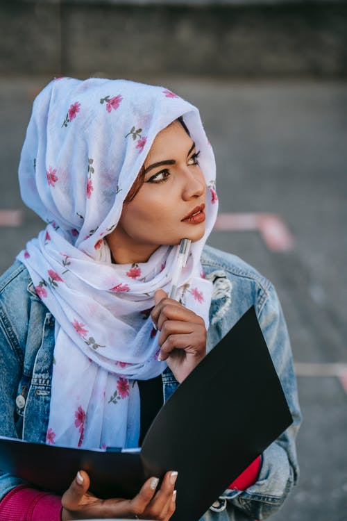 Muslim female student with documents in folder in hand looking away