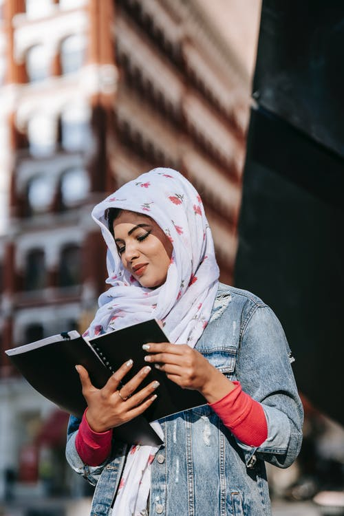 Low angle of focused Muslim female in trendy clothes and headscarf reading documents in black folder while standing on city street against high raise building in sunny day