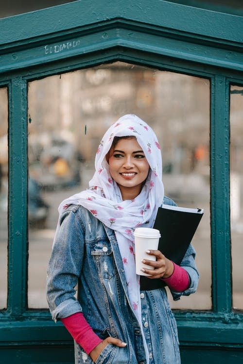 Smiling Muslim woman with documents in folder and takeaway cup