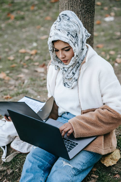 Woman in White Hijab Using Black Laptop Computer