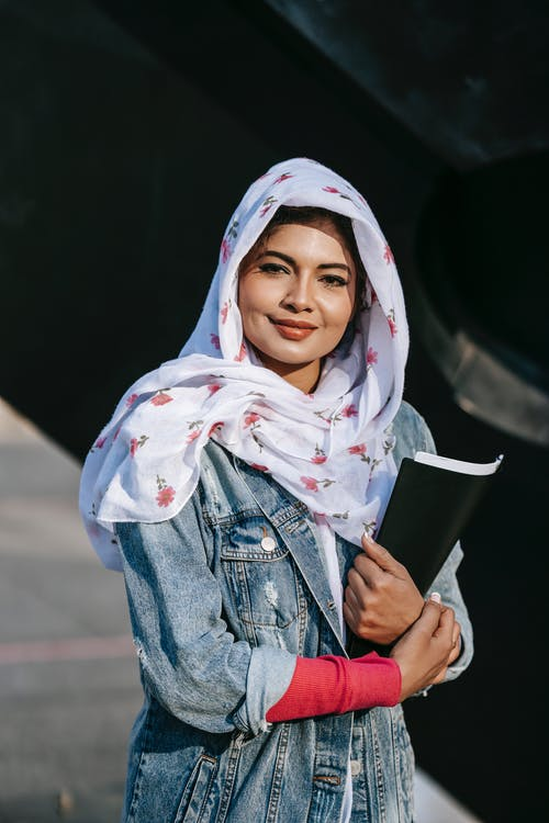 Positive ethnic lady carrying folder with documents and standing in sulight
