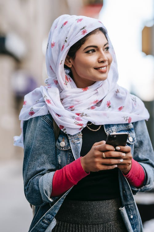 Positive young lady wearing headscarf surfing smartphone while walking along street