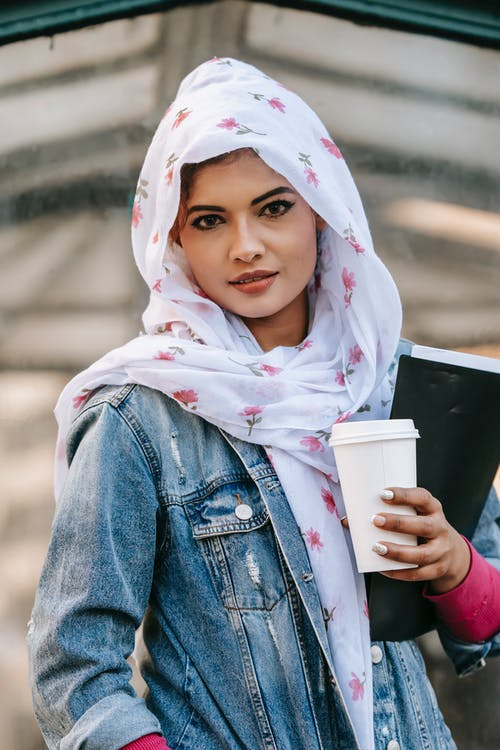 Ethnic woman wearing headscarf while standing with coffee to go and folder