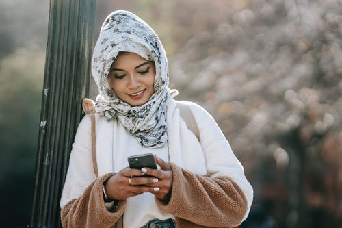 Cheerful young ethnic female in headscarf and coat browsing smartphone