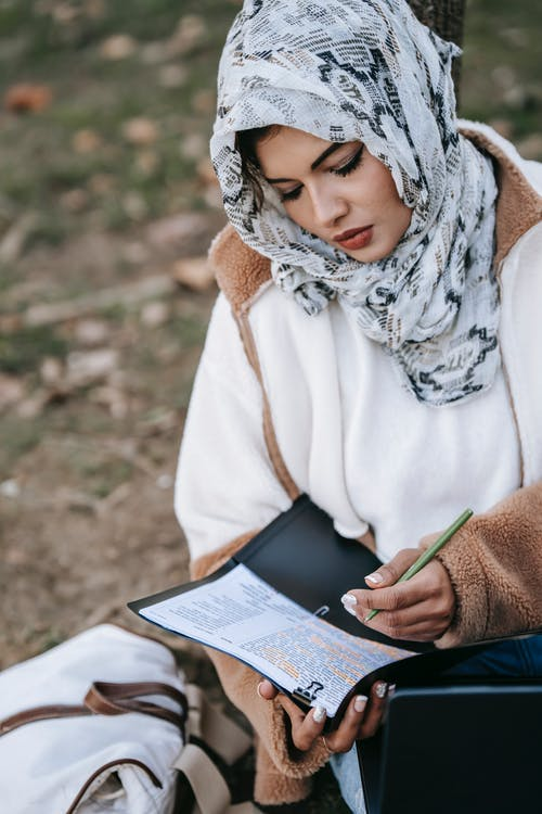Concentrated ethnic woman in hijab writing notes in project
