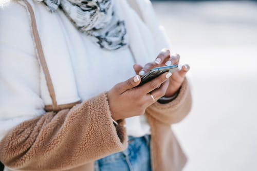 Crop anonymous woman wearing fluffy warm jacket and scarf using contemporary smartphone while standing outdoors