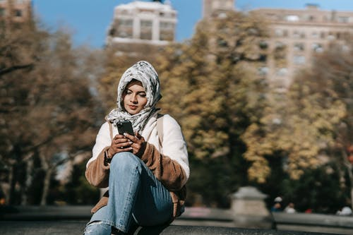 Young ethnic woman using smartphone while sitting in city park