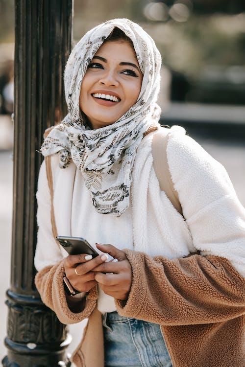 Happy stylish ethnic lady smiling on city street