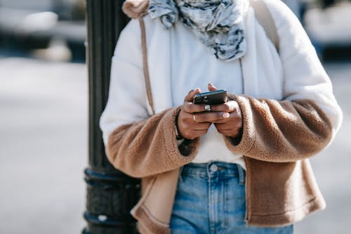 Crop unrecognizable woman in trendy warm outfit using mobile phone while standing on city street near metal pillar