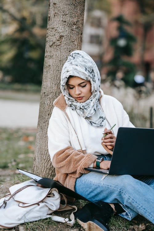 Concentrated young Muslim female student in trendy outfit and hijab reading documents and using laptop while doing homework assignment sitting near tree in park