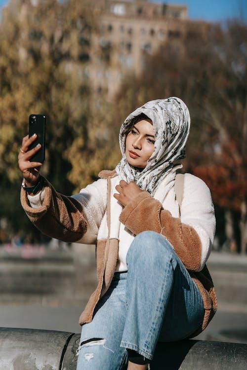 Trendy young Muslim lady taking selfie in city park