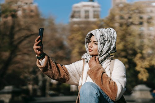 Gorgeous young Muslim female millennial in trendy outfit and hijab resting in autumn park and taking selfie on smartphone