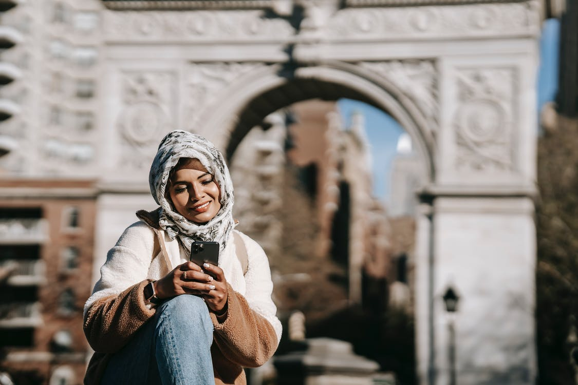 Self assured young ethnic female in stylish clothes and Muslim headscarf smiling while messaging on smartphone sitting in city square near aged arch