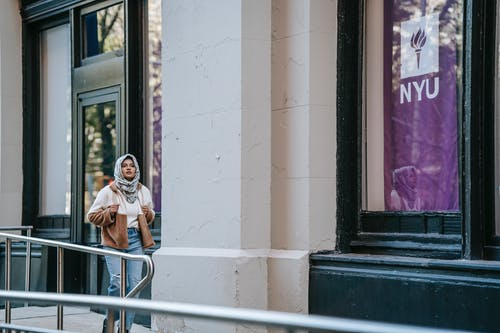 Trendy young Muslim woman walking on city street