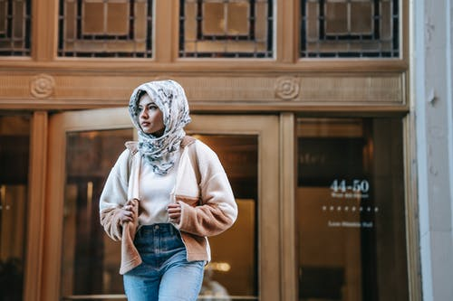 Serious young graceful ethnic lady in stylish clothes and traditional hijab standing near wooden doors of old building and looking away thoughtfully