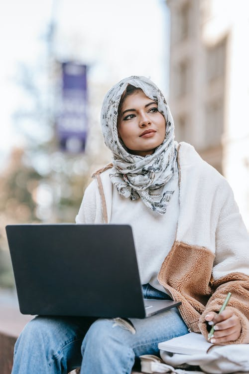 Young Muslim female freelancer in trendy clothes and hijab looking away thoughtfully while taking notes and using laptop during remote work on city street