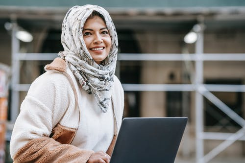 Joyful young Arab female freelancer in casual outfit and hijab smiling while working remotely on netbook on city street
