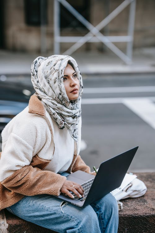 Concentrated young ethnic female looking away while working distantly on laptop on street