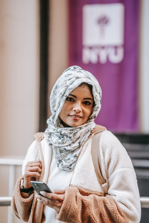 Self esteem young Muslim female millennial in trendy outfit and traditional headscarf smiling and looking at camera while browsing smartphone on city street