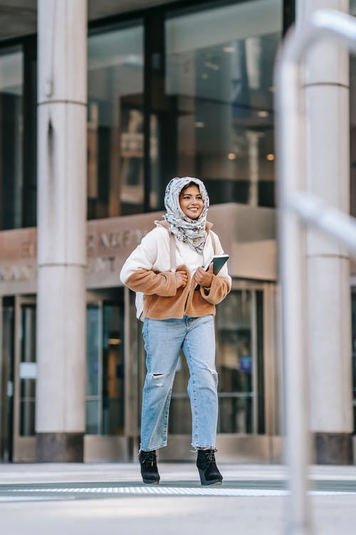 Happy ethnic female student smiling and walking on city street