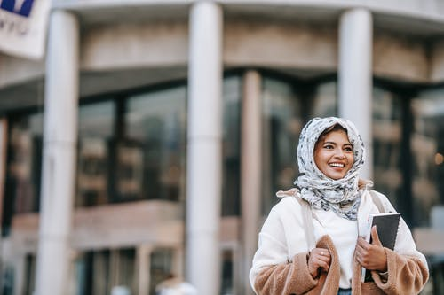 Self assured young ethnic lady with copybooks in hand smiling on street