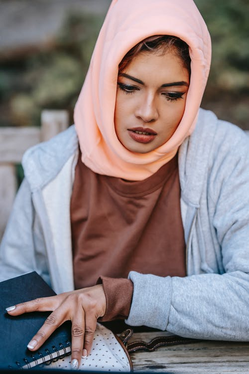 Serious young Muslim lady in traditional headscarf working with notebook in park