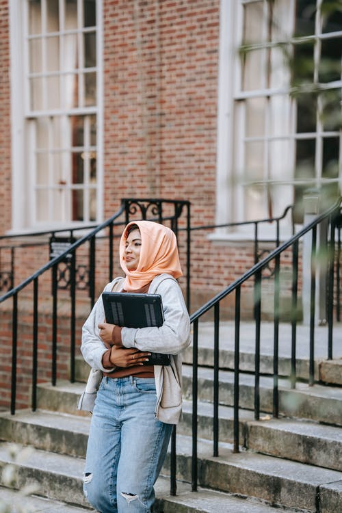 Positive young Muslim woman wearing trendy jeans and traditional hijab carrying portable laptop leaning on metal railing of staircase near university