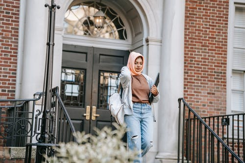 Young Muslim woman wearing jeans and orange hijab carrying backpack and laptop walking down stairway after studies in university