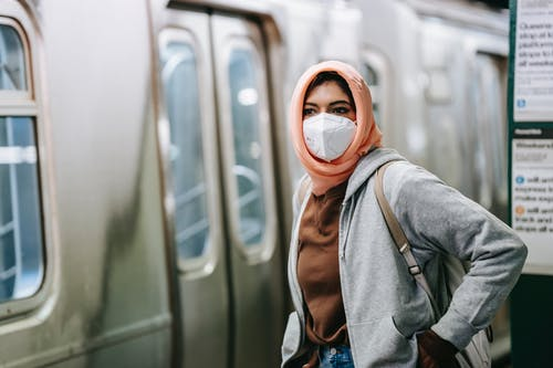 Young Muslim female in casual wear and traditional headscarf with protective mask on subway platform