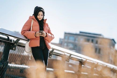 オレンジ色のジャケットと橋の上に立っている黒いズボンの女性